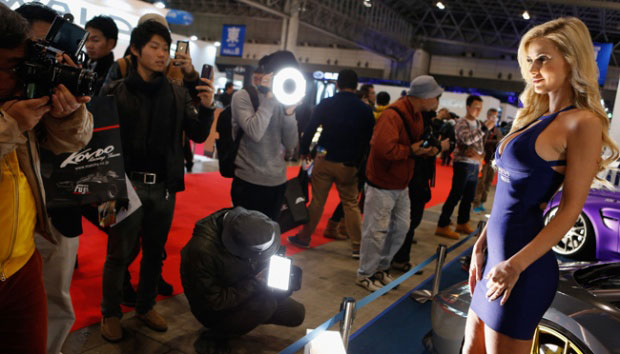 Seorang model berpose di hadapan sejumlah pengunjung yang ingin mengambil gambar dirinya saat berpose di samping mobil-mobil modifikasi dalam pameran Tokyo Auto Salon Car 2016 di Chiba, Jepang, 15 Januari 2016. (Christopher Jue/Getty Images)